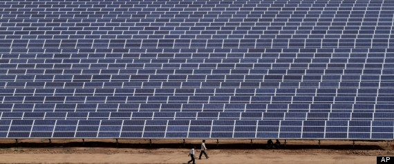 In this Saturday, April 14, 2012, file photo, Indian workers walk past solar panels at the Gujarat Solar Park at Charanka in Patan district, about 250 kilometers (155 miles) from Ahmadabad, India  AP PHOTO